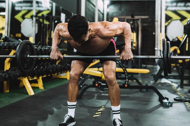 Homem forte levantando peso com a barra em uma academia