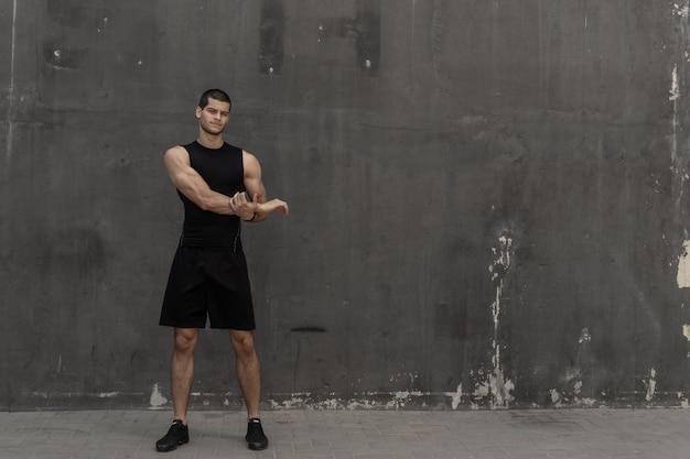Homem forte, musculoso e desportivo, aquecendo, preparando-se para o treinamento