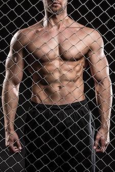 Homem forte na cerca com correntes