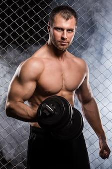 Homem forte na cerca com um haltere