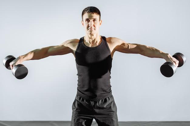Homem forte novo que exercita com pesos no gym.
