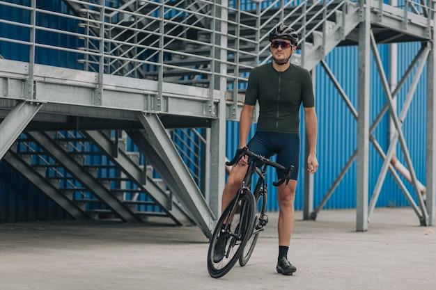 Homem forte posando na rua com bicicleta preta