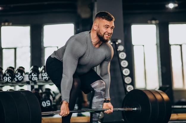 Homem forte se exercitando na academia