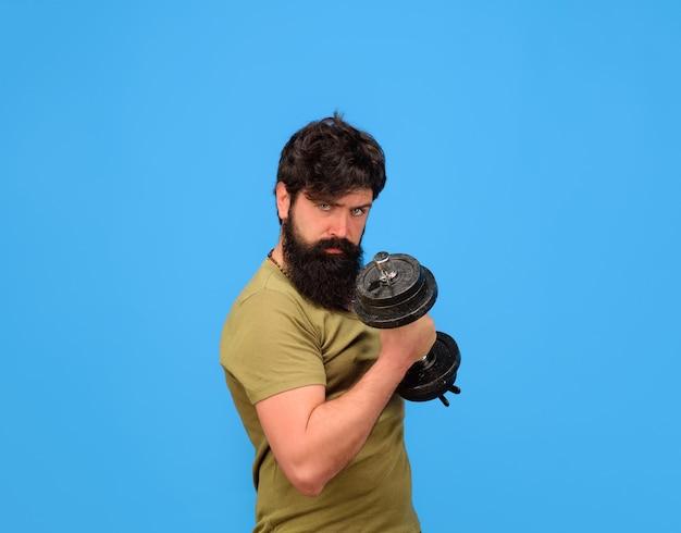 Homem forte segura halteres musculoso desportista com halteres treinando no ginásio bonito atleta homem