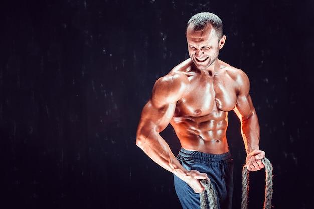Homem forte sem camisa fisiculturista malhando duro com corda