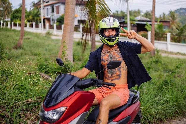 Homem forte tatuado em campo de selva tropical com moto vermelha