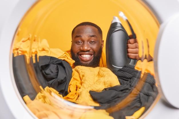 Homem fotografado de dentro de uma máquina de lavar segura uma garrafa de detergente líquido cercada por pilhas de roupas posa na lavanderia