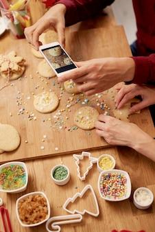 Homem fotografando biscoitos de natal
