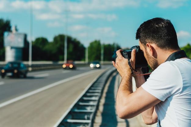 Homem fotografando carros na estrada.