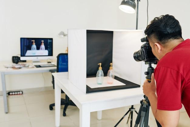 Homem fotografando garrafas em um cubo de luz