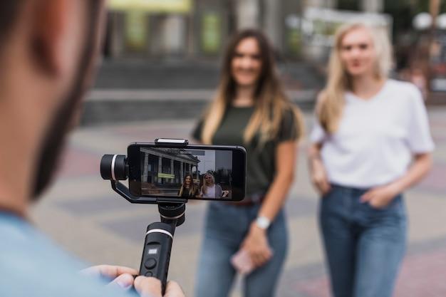 Homem fotografando mulheres com telefone