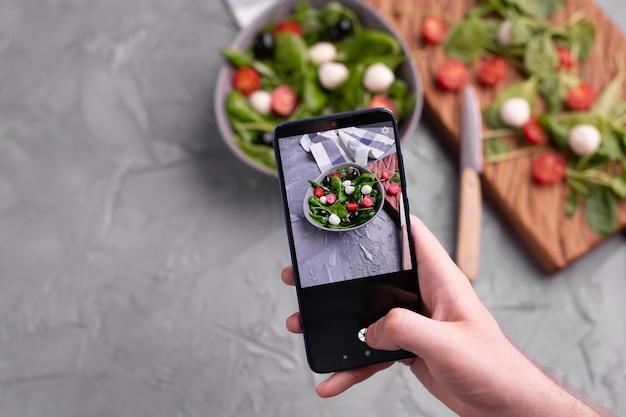 Homem fotografando salada de legumes com mussarela e espinafre na câmera do celular, cozinhando blogs