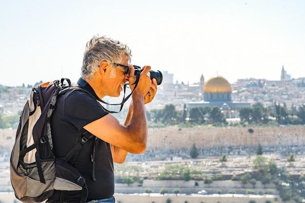 Homem fotografando turistas em jerusalém
