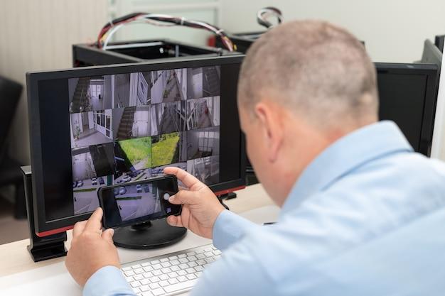 Homem fotografando vários monitores na sala de vigilância cctv management