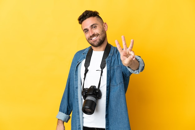 Homem fotógrafo isolado em amarelo feliz e contando três com os dedos