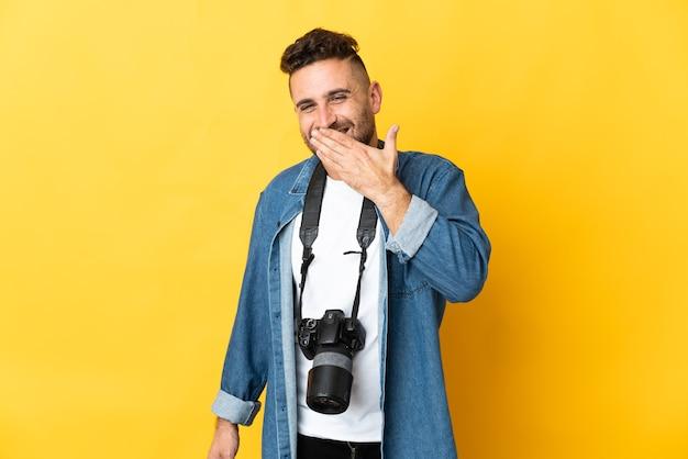 Homem fotógrafo isolado em um fundo amarelo feliz e sorridente, cobrindo a boca com a mão