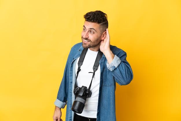 Homem fotógrafo isolado ouvindo algo colocando a mão na orelha