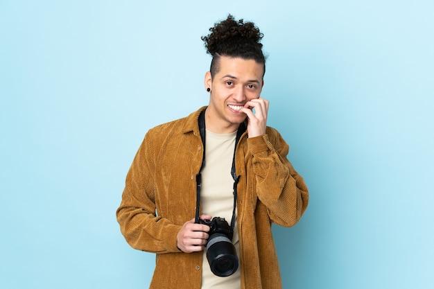 Homem fotógrafo sobre fundo azul isolado nervoso e assustado