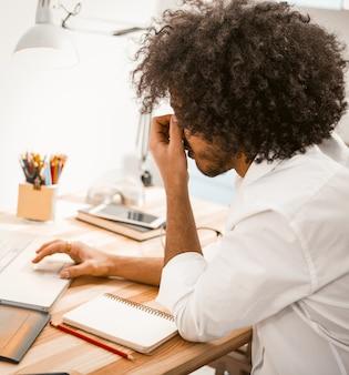 Homem freelance cansado trabalhando duro no laptop e precisa descansar. vista lateral do cara criativo com penteado desgrenhado, esfregando o nariz cansadamente. imagem enfraquecida