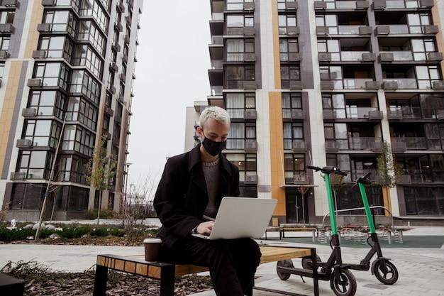 Homem freelancer concentrado na máscara facial preta, trabalhando do lado de fora no parque e usando seu laptop moderno. ele se senta no banco e escreve um programa. duas scooters elétricas perto do banco. blocos de apartamento.