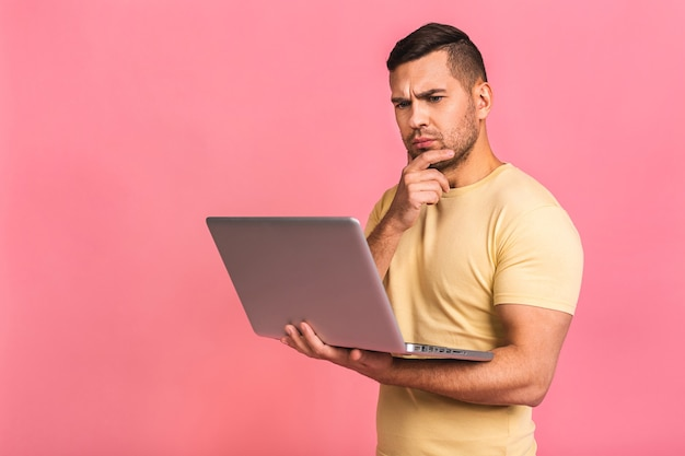 Homem freelancer interessado inteligente focado e interessado segurando um laptop com as mãos trabalhando em um projeto de prazo