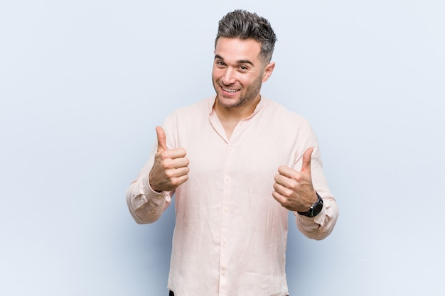 Homem fresco considerável novo que aumenta ambos os polegares acima, sorrindo e seguro.