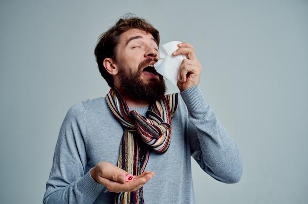 Homem frio com um lenço no pescoço gripe, problemas de saúde, luz de fundo