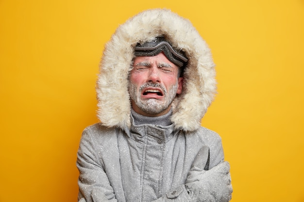 Homem frio estressado chora de desespero tem expressão facial desagradável rosto congelado coberto de gelo usa jaqueta cinza.