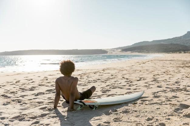 Homem frio sentado na praia com prancha de surf