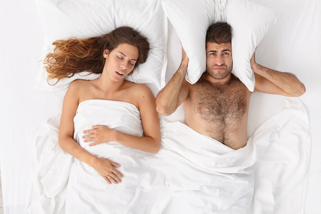 Homem frustrado cobre os ouvidos com travesseiro, não consegue dormir por causa do ronco alto da esposa, sofre de insônia, posa no quarto. homem cansado irritado com o ronco da mulher. pessoas, saúde, distúrbios do sono