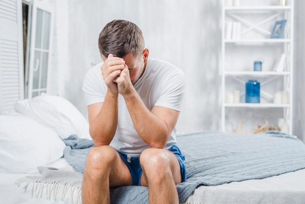 Homem frustrado com dor de cabeça, sentado na cama em casa