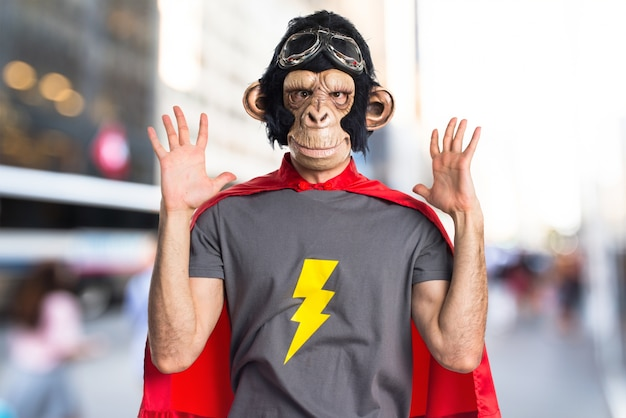Homem frustrado do macaco do super-herói no fundo não focado