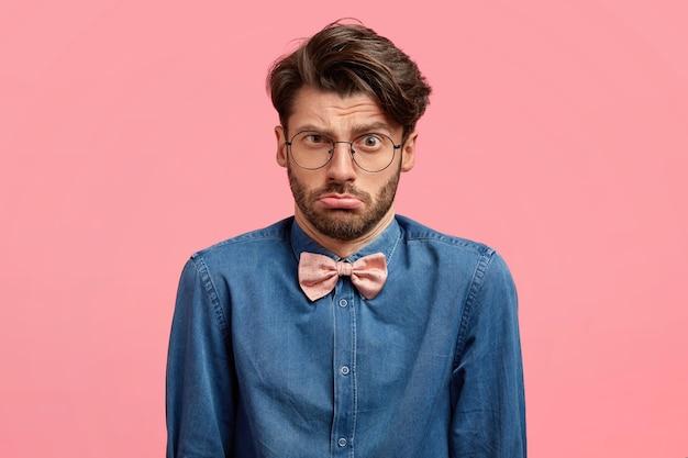 Homem frustrado e descontente com penteado da moda, franze o lábio inferior, expressão facial indecisa e insatisfeita