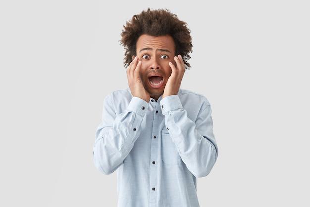 Homem frustrado e intrigado com expressão assustada, reage a notícias negativas repentinas, toca o rosto, sente-se ansioso
