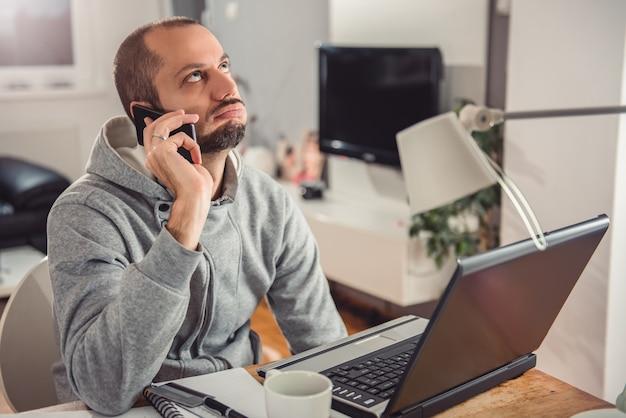 Homem frustrado, falando no telefone inteligente