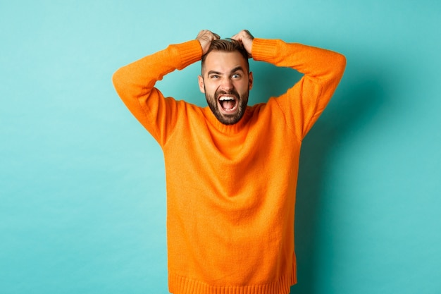 Homem frustrado gritando, arrancando cabelos e gritando com raiva, perdendo a paciência e parecendo louco, de pé sobre uma parede turquesa clara.
