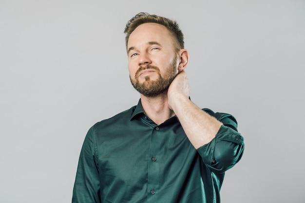Homem frustrado, segurando a mão no pescoço, com dores nas costas
