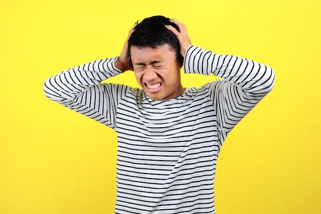Homem frustrado segurando sua cabeça. jovem asiático fazendo o gesto de um homem frustrado segurando a cabeça dele, isolada em um fundo amarelo
