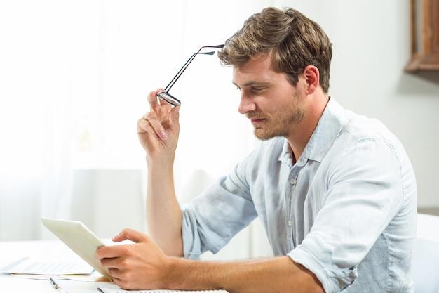 Homem frustrado usando tablet digital no escritório
