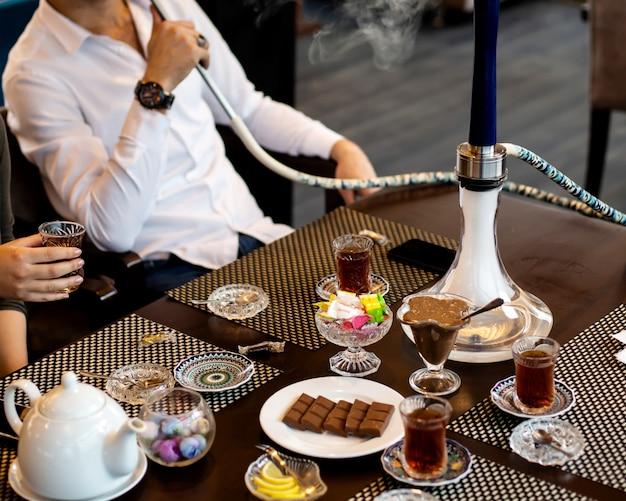 Homem fuma cachimbo de água e mulher bebe chá