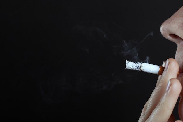 Homem fuma um cigarro em um espaço de cópia de close-up de fundo escuro, risco para a saúde, danos ao corpo pelo uso de tabaco, mau hábito.