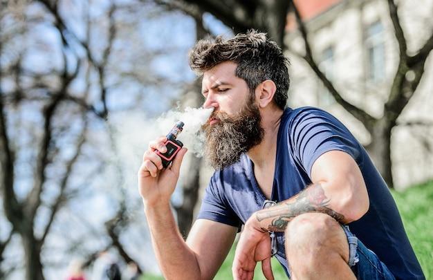 Homem fumando cigarro. hipster maduro com barba. homem moderno segurar o dispositivo vaping. cigarro eletrônico de fumo masculino brutal barbudo. segurança da saúde e dependência. inalar o vapor. robusto e viril.