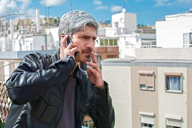 Homem fumando e conversando com seu smartphone no terraço do edifício