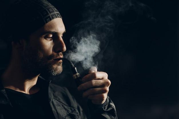 Homem fumando um cachimbo no escuro. retrato de perfil.