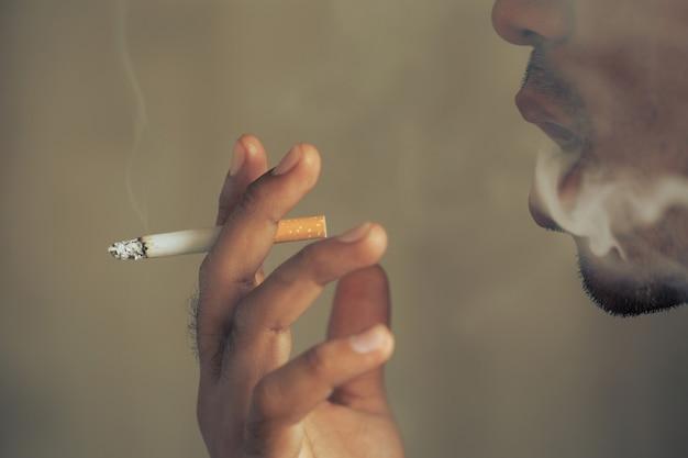 Homem fumando um cigarro. a fumaça do cigarro se espalhou.
