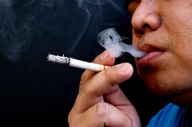 Homem fumando um cigarro, imagem do cigarro na mão com fumaça