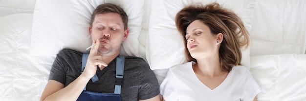 Homem fumante com cigarro deitado na cama com a esposa dormindo hábitos ruins e fumando na cama