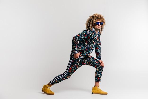 Homem funky de sorriso positivo adulto com penteado encaracolado nos suglasses e na roupa do vintage que levanta no fundo branco do estúdio.