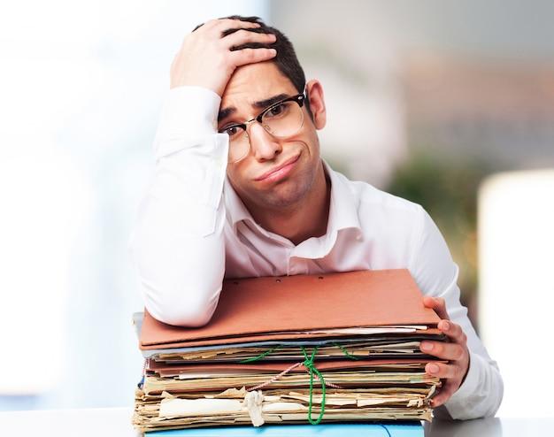 Homem furado olhando para uma pilha de papéis com uma mão na testa