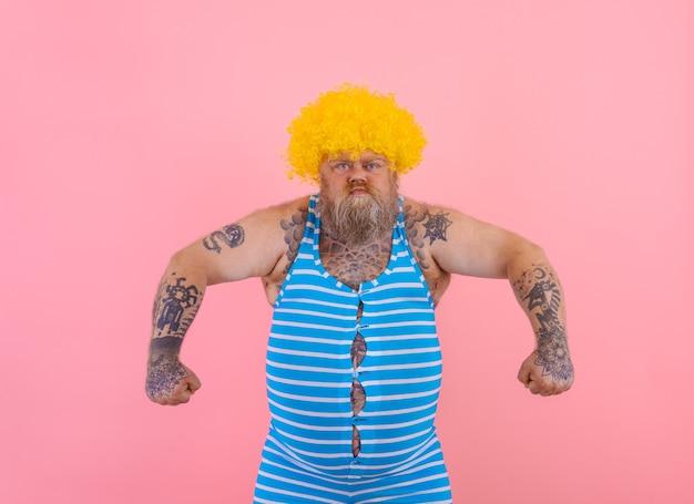 Homem furioso com peruca amarela e maiô pronto para o verão